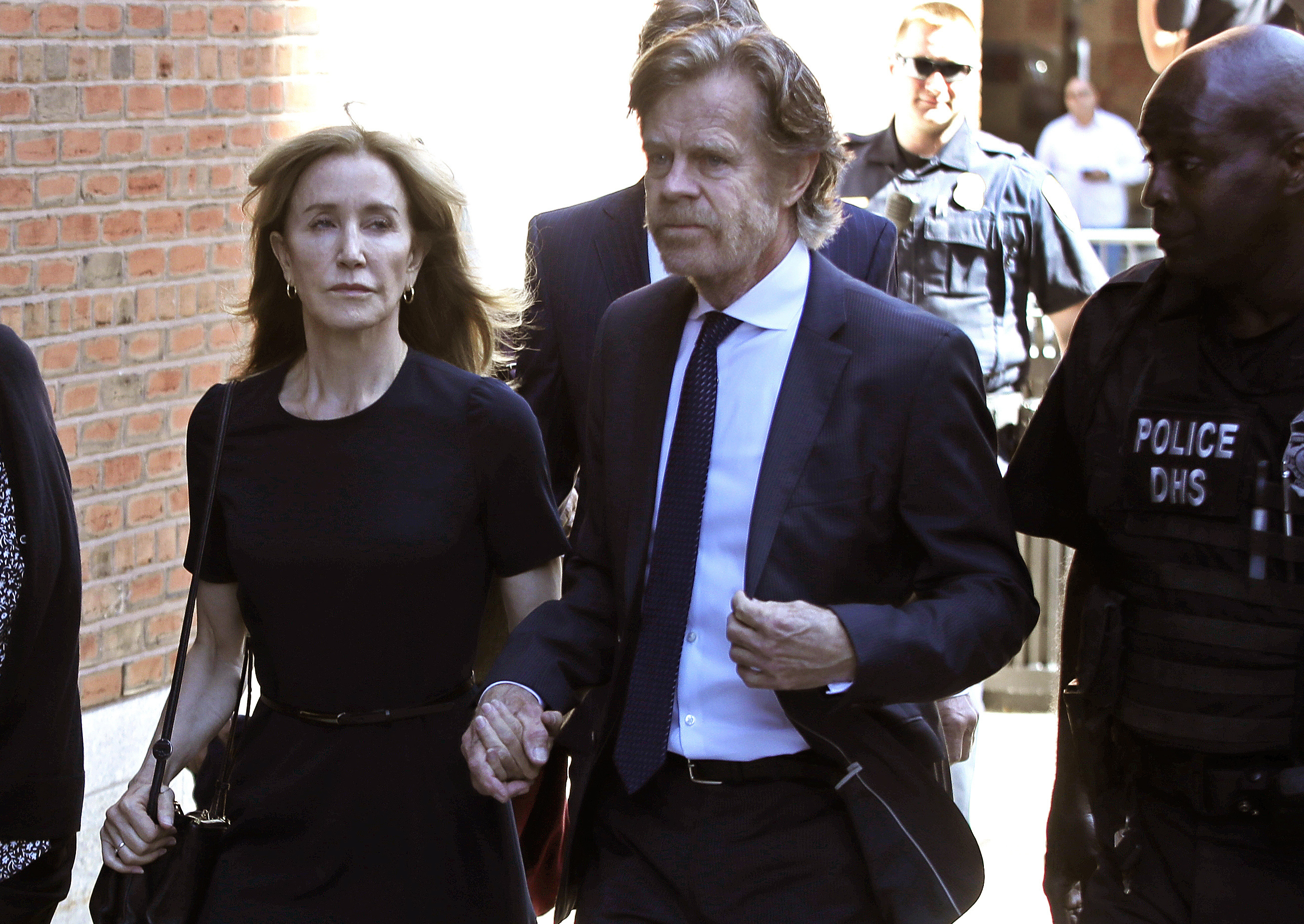 Felicity Huffman arrives at federal court with her husband William H. Macy for sentencing in a nationwide college admissions bribery scandal, Friday, Sept. 13, 2019, in Boston. (AP Photo/Elise Amendola)