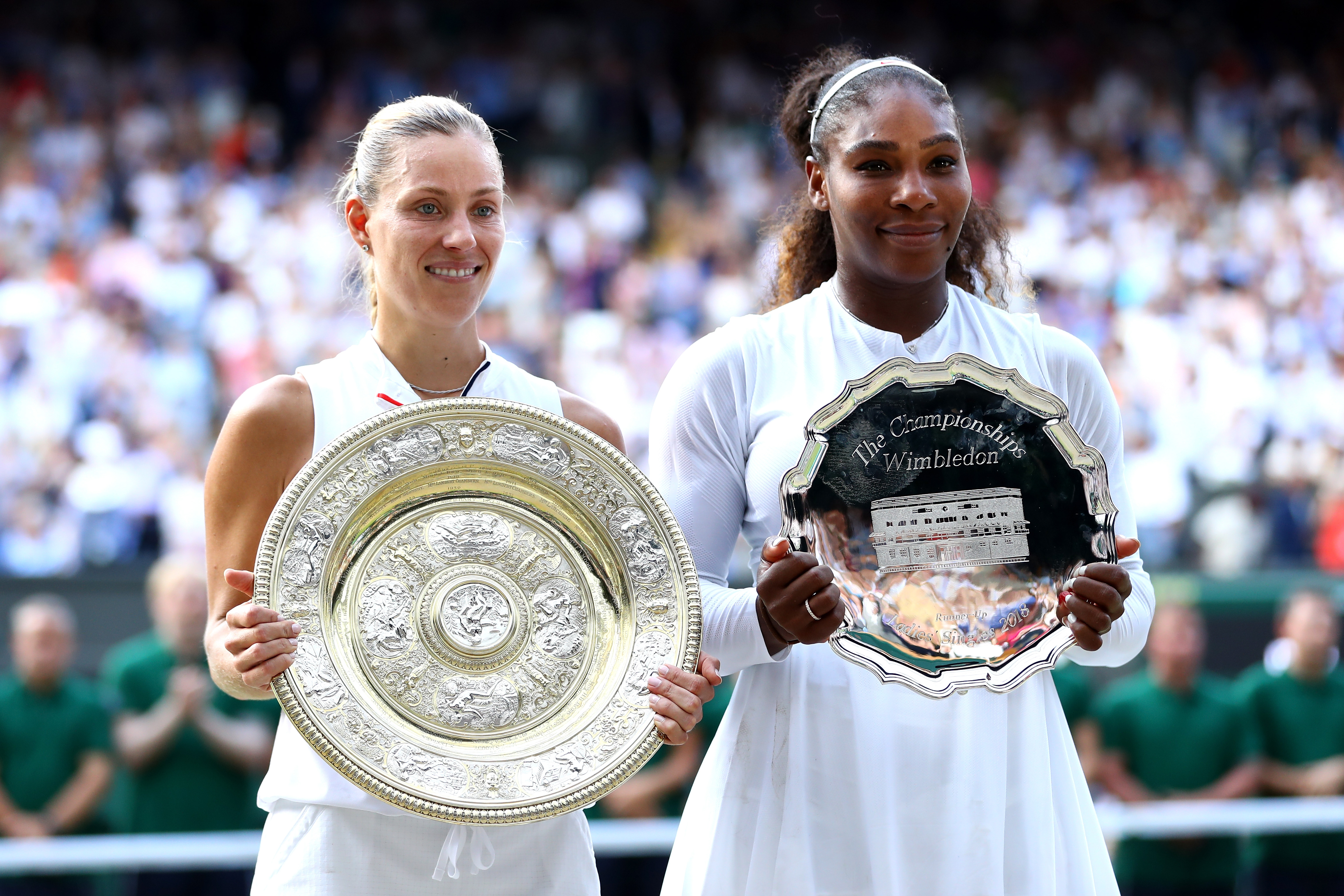 Winner Angelique Kerber of Germany and runner-up Serena Williams of The United States pose with the trophies after the Ladies' Singles final on day twelve of the Wimbledon Lawn Tennis Championships at All England Lawn Tennis and Croquet Club on July 14